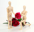 Wooden figurine man holding and giving rose to lover with rose b Royalty Free Stock Photo