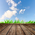 Wooden floor and blue sky textured green grass with Royalty Free Stock Image
