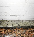 Wooden floor or boardwalk a walk with fallen fall leaves off of the surface of the Stock Photo