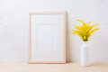 Wooden frame mockup with ornamental yellow flowering grass in va