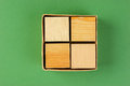Wooden geometric cube in a box on green background Stock Image