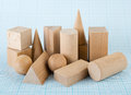 Wooden geometric shapes on graph paper Royalty Free Stock Photography