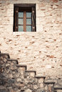 Wooden and glass window in a stone wall with stairs Royalty Free Stock Photo