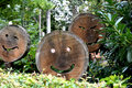 Wooden happy faces carved in round cut wood trunk Stock Image