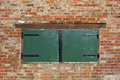 Wooden hatch a green painted boarded up window or in a red brick wall background Stock Images