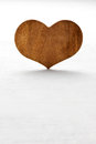 Wooden heart balanced upright on its tip on a white background symbolic of valentines love and romance with copyspace Stock Images