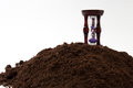Wooden hourglass on the soil ground Royalty Free Stock Photo