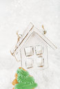 Wooden house christmas decoration on white snow background and green cookie Stock Images