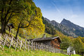 Wooden house with crucifix and chapel in the mountains Royalty Free Stock Image