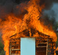 A Wooden house in flames Royalty Free Stock Photo