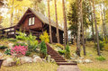Wooden house in forest chalet style the with rockery garden and steps leading to the entrance Royalty Free Stock Photos