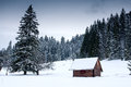 Wooden house in forest at winter time Royalty Free Stock Photo