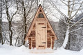 Wooden house from log, with red roof in winter forest Royalty Free Stock Photo