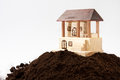 Wooden house model on the pile of soil Royalty Free Stock Photo