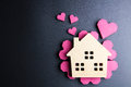 Wooden house toy and paper box red heart shape on black backgrou