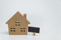 Wooden house toy and small black board with white background and selective focus Royalty Free Stock Photo