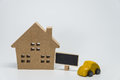 Wooden house, yellow car toy and small black board with white background and selective focus Royalty Free Stock Photo
