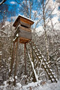 Wooden hunting tower in winter landscape near forest Stock Photo
