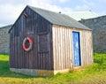 Wooden hut with blue door.