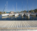 Wooden jetty in marina empty on the lake shore with yachts moored Royalty Free Stock Images