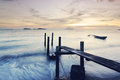 Wooden jetty during sunset with sea Stock Images