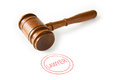 A wooden judge s gavel with a red lawyer stamp against a white background Royalty Free Stock Photos
