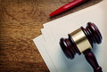 Wooden judges gavel and blank paper or auctioneers white lying on a desk with a ballpoint pen in a concept of judgements or Royalty Free Stock Images