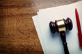 Wooden judges gavel and blank paper or auctioneers white lying on a desk with a ballpoint pen in a concept of judgements or Royalty Free Stock Photos