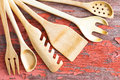 Wooden kitchen utensils arranged in a fan assorted set of handcrafted from the top left corner on grunge picnic table Royalty Free Stock Image
