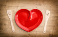 Wooden kitchen utensils and red heart plate. Funny tools Royalty Free Stock Photo