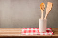 Wooden kitchen utensils on table with tablecloth over grunge wall background with copy space for product montage