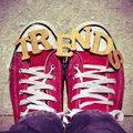 Wooden letters forming the word trends and the feet of a young man high angle shot some wearing red sneakers on street Stock Photography
