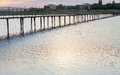 Wooden long bridge over a sea plait, river at sunset in perpekti Royalty Free Stock Photo