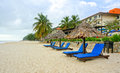 Wooden lounge deck chairs and umbrella on paradise beach looking out to ocean blue sky Stock Photos