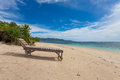 Wooden lounger lonely beach tropics Royalty Free Stock Photos