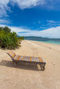 Wooden lounger on lonely beach in the tropics Stock Image