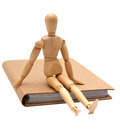 Wooden man sitting on brown notebook Royalty Free Stock Photo
