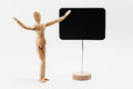 Wooden mannequin pointing on a canvas as presenting something Stock Photography