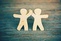 Wooden men holding hands little on boards background symbol of friendship love and teamwork Stock Photography