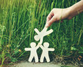 Wooden men holding hands little in natural grass symbol of friendship love teamwork or ecology concept Stock Image