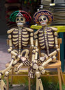Wooden mexican skeletons handicrafts of carved with hats sombreros for day of the dead Stock Photos