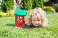 Wooden model of house and little blonde girl lying on grass green real estate concept Royalty Free Stock Images