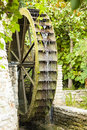 Wooden old mill wheel visible stream of falling water from paddles Stock Photo