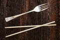 Wooden pairs of chopsticks vs fork. Abstract conceptual image Royalty Free Stock Photo