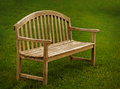 Wooden park bench a with green grass Royalty Free Stock Images