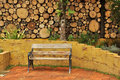 Wooden park bench in a log wall Royalty Free Stock Image