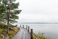 Wooden path on a lakeshore going along the calm lake Stock Photos