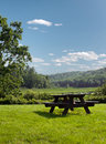 Wooden picnic table on green grass landscape Royalty Free Stock Photos