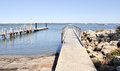 Wooden pier and boat launch area on the river s edge with rocks at mandurah s foreshore in western australia Royalty Free Stock Photos