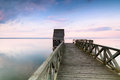 Wooden pier on calm lake at sunset colorful over viewed from a bridge Stock Photography